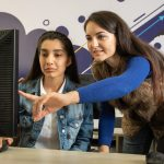 two women looking at front of pc screen