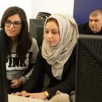Two female annotators work together on a computer in the Humans in the Loop office